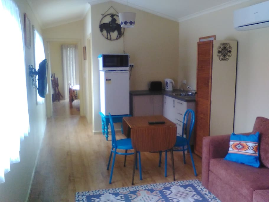 Kitchen with fridge, microwave, toaster, electric jug, sink, crockery and cutlery.