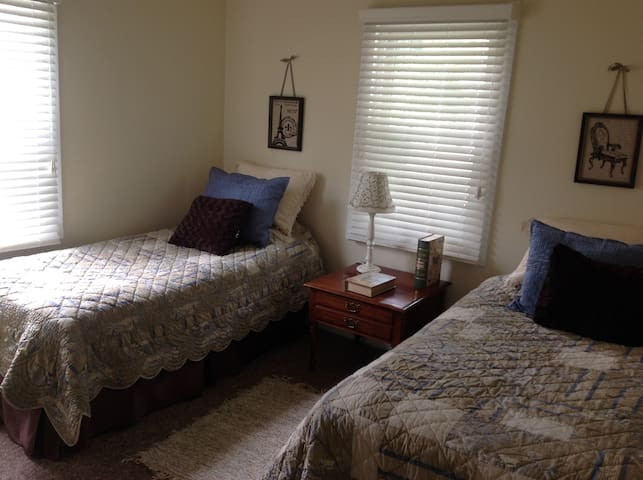 Twin beds with French quilt bedding and lots of light!
