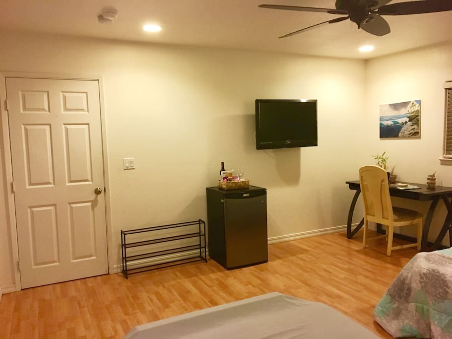 (View from the beds) shoe rack, mini fridge, basket filled with snacks and wine, & television