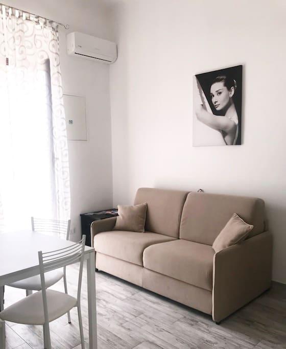 Una parte della zona giorno con comodo divano-letto + aria condizionata e accesso al balcone