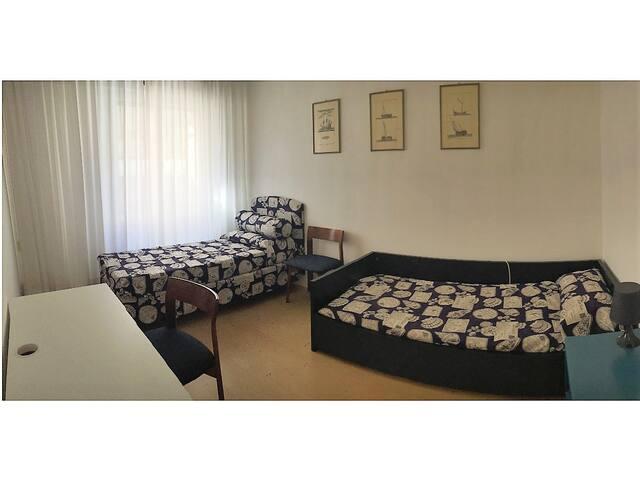 Camera da letto 2 con 2 letti singoli, scrivania e grande finestra con tapparelle e armadio