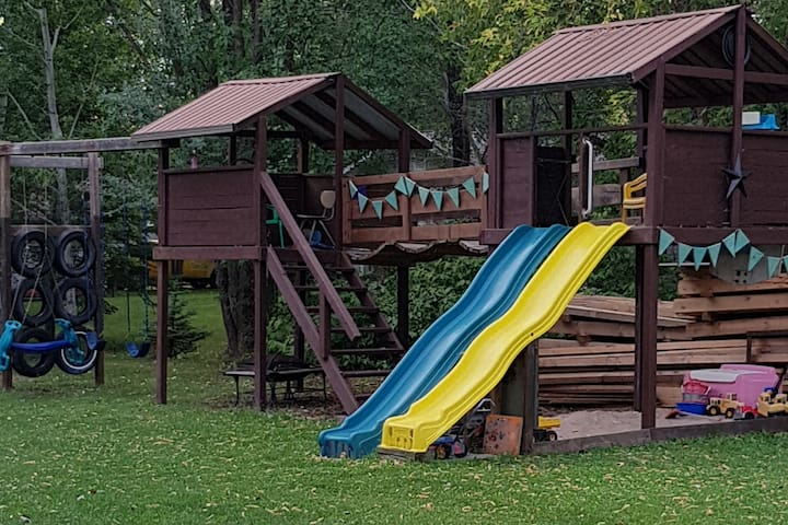 Large play structure with wooden bridge and sand box with toys