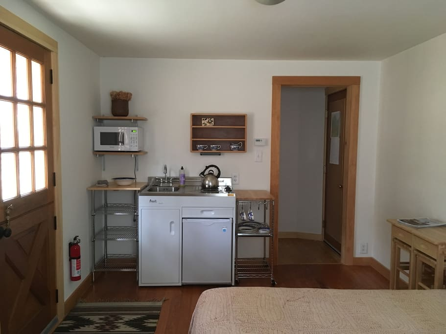 Studio entranceway, kitchenette (with stovetop, sink, mini-fridge, microwave and tea/coffee-makers) and hallway to full bath