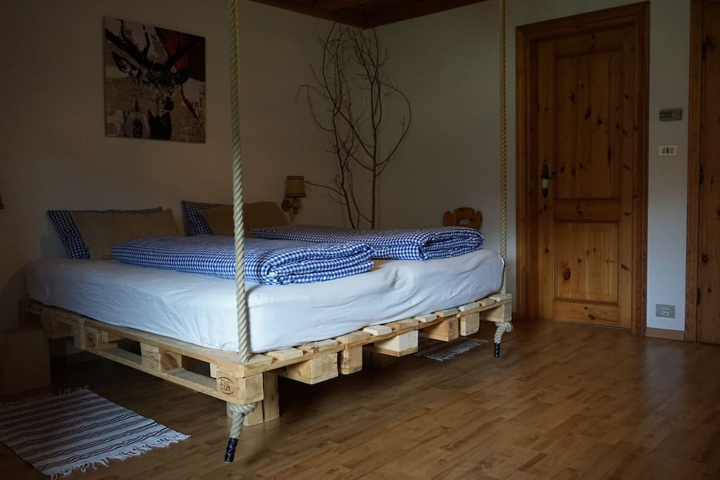 Double bed with a sheep wool mattress hanging from the ceiling for an extra good sleep
