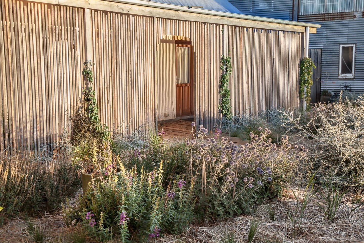 This is the Orto straw cottage, protected by a wooden facade. As the sun sets, the light filters through to create a beautifully lit walkway.