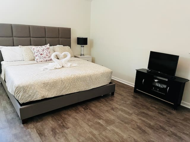 """Master Bedroom - King size comfy bed with nightstand, table lamp and 32"""" Smart TV with cable."""