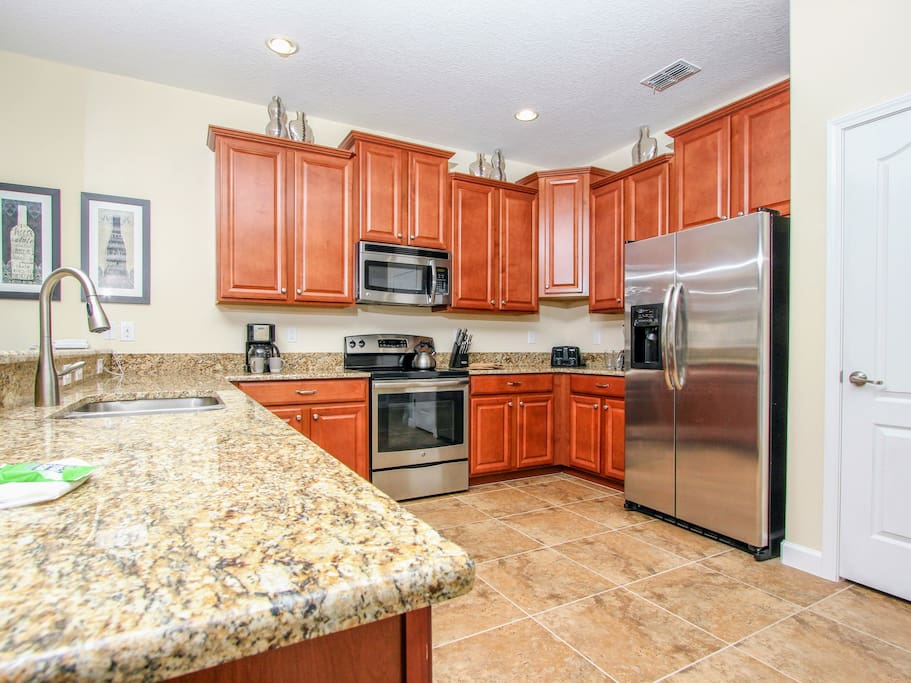 Open concept kitchen with granite countertops & stainless steel appliances
