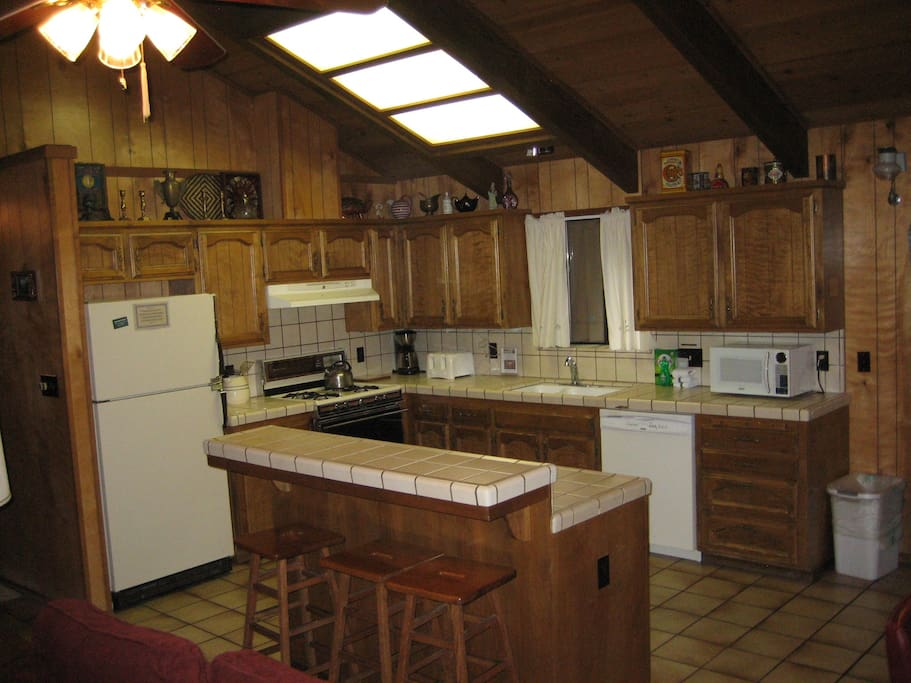 View of kitchen from living room area showing counter seating.