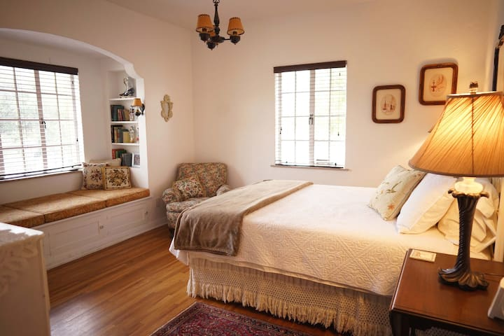 Romantic front bedroom has window seat for lounging with one of our vintage books.