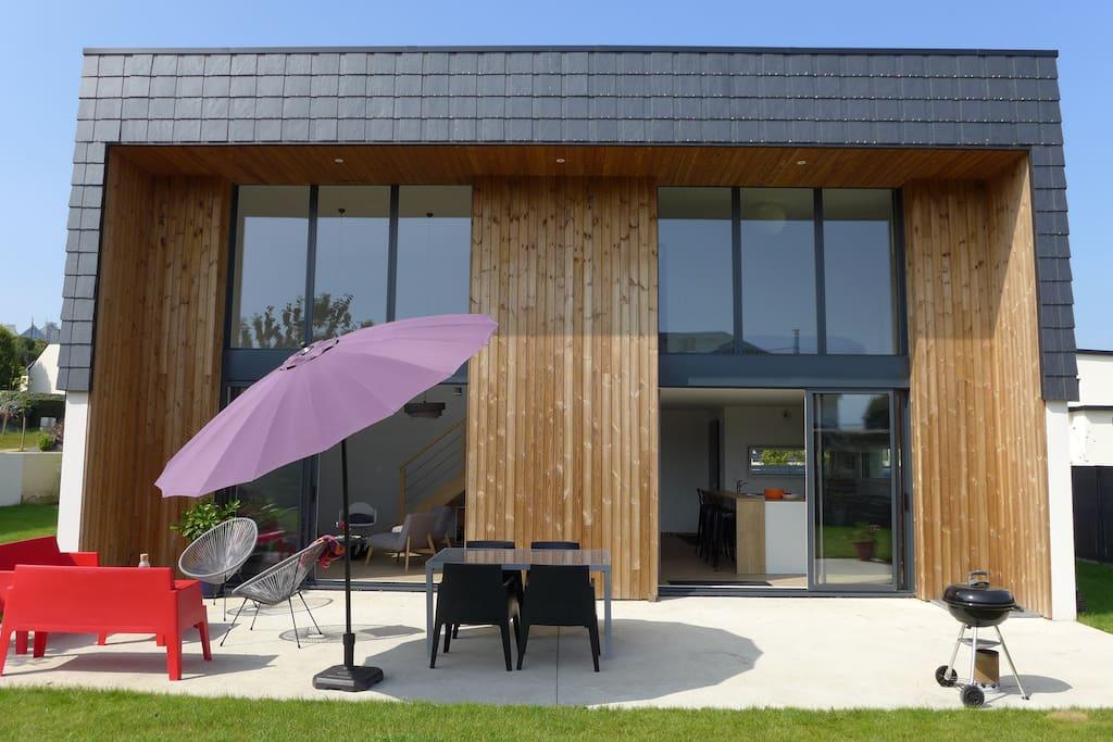 Les baies vitrées permettent à la villa d'être très lumineuse et ouvrent sur une grande terrasse et un jardin privatif clos.