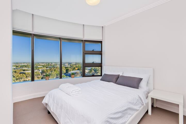 Queen bed with Olympic Park View