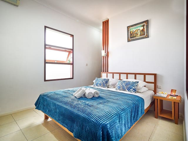 Bedroom with queen bed size completed with Air Conditioner