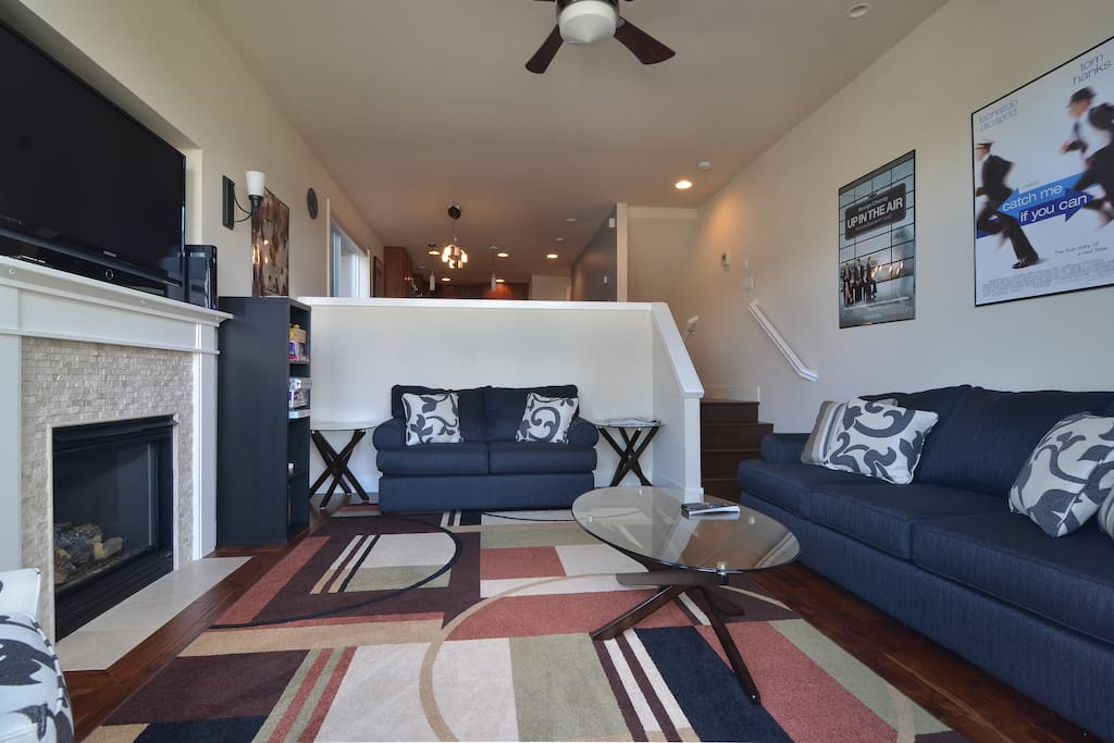 The sunken living room features a gas fireplace, large screen television, and sleeper sofa.
