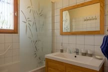 Salle de bain situé au rez-de-chaussée, baignoire avec barre d'appuie, pare-douche, vasque & meuble ainsi qu'un siège de douche amovible
