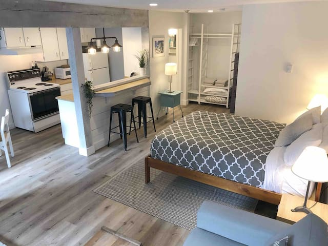Open stuido suite including full kitchen, dining table, full bathroom, queen bed, and a secondary queen mattress for extra guests.
