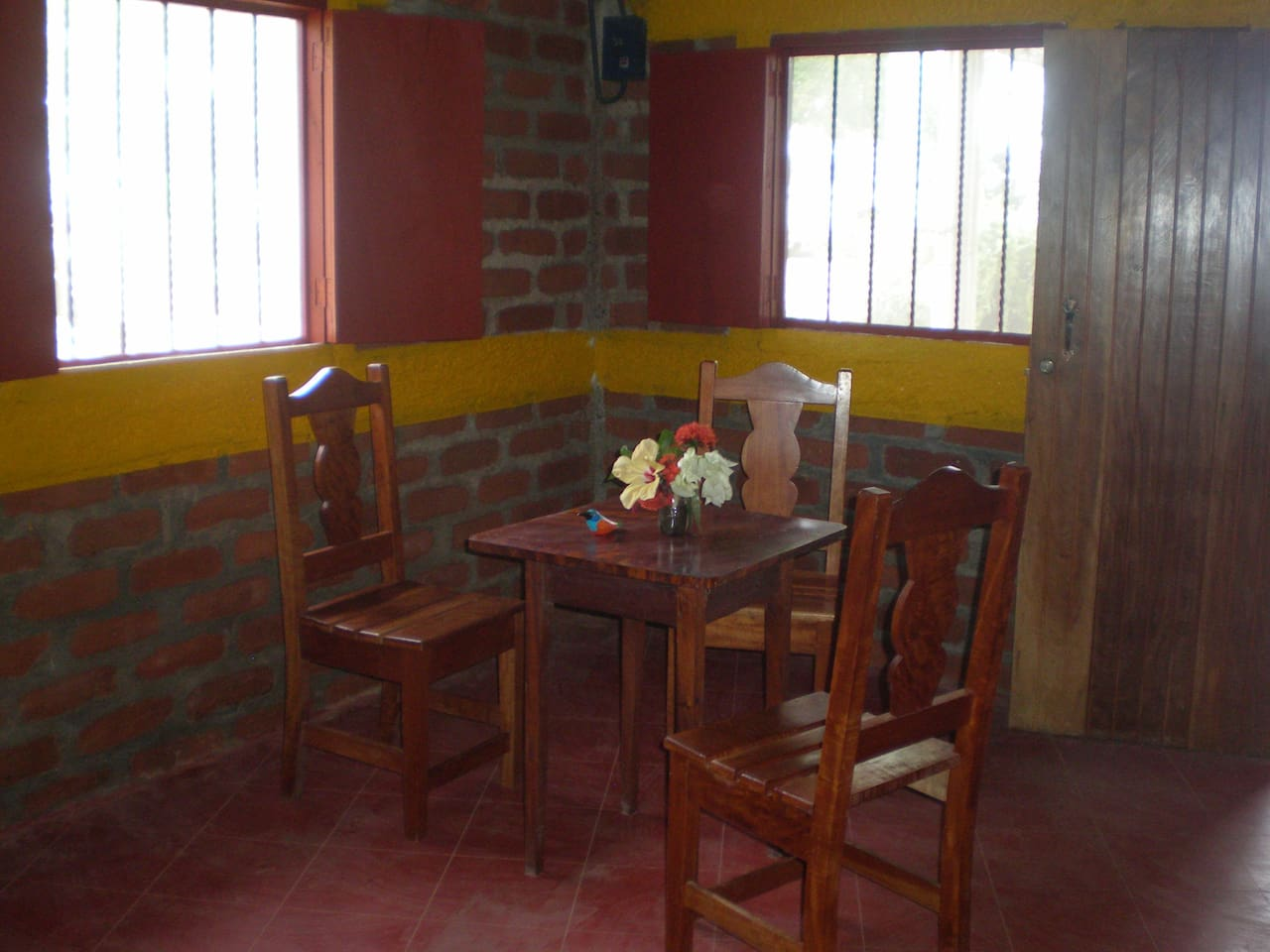 Dining area with table and chairs, rocking chairs and hammock - many screened windows and screened door