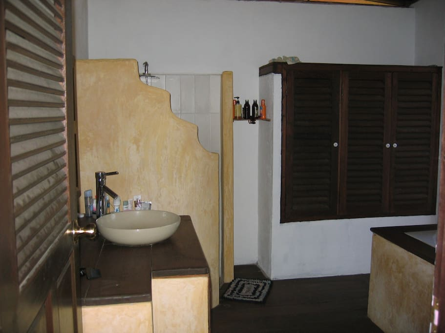 bathroom with shower and bathtub. door to outside shower and garden.