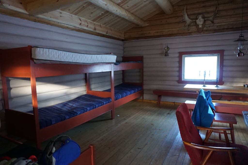 Combined living and sleeping room, with 2 bunk beds, and one single bed.
