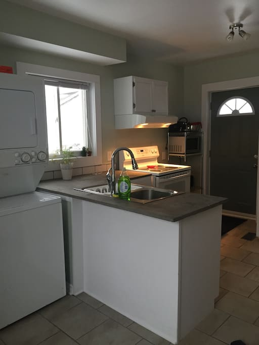 Kitchen. Modern, clean concrete counters. Washer and dryer.