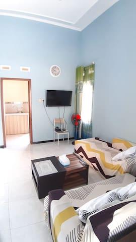 Ruang tengah dilengkapi sofa, TV dan meja makan