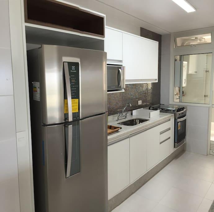 Cozinha equipada com geladeira, fogão, microondas, sanduicheira, cafeteira e todos os utensílios como louças, talheres, copos e demais itens de cozinha.