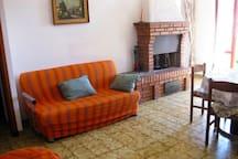 Sala da pranzo e soggiorno con divano e poltrone