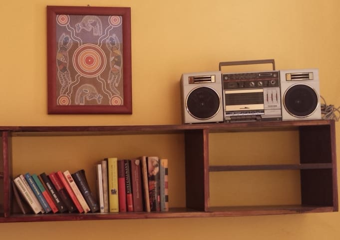 A private sitting room with a shelf for your books and a radio.