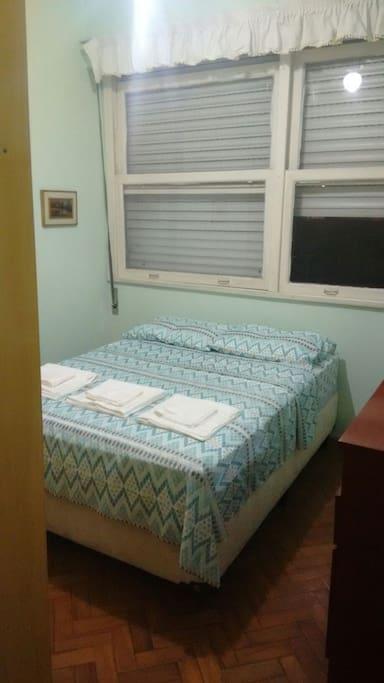 Quarto com cama de casal, ventilador de teto e chave na porta.