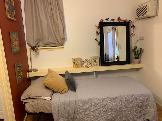 A cozy space with a twin sized bed and rolling table great for a laptop. With quality linens and pillows as well as a memory foam mattress topper, it's a great sleeping area! A self controlled AC unit allows you to control the temperature.