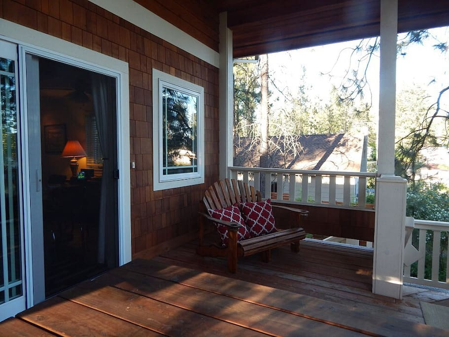 Large covered front deck of Guesthouse with BBQ, picnic table, and comfortable views of lake.