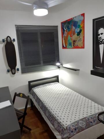 Quarto de solteiro compacto, com decoração estilo jovem, com mesa de estudo e gavetas para roupas, luminária para leitura e ventilador de teto com controle remoto.