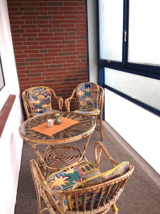 Verglaster Balkon mit Esstisch und zu öffnenden Fenstern