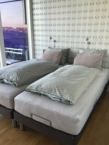 The first bedroom with access to a balcony with morning sun
