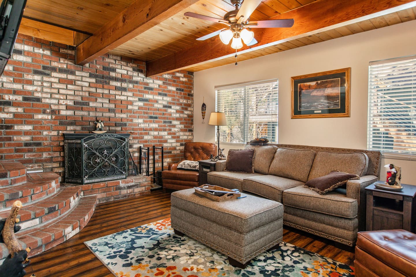 Welcome to Chateau Sasquatch! Enjoy the rustic & cozy downstairs living room with wood burning fireplace, sofa, oversized chair, ceiling fan, & TV (Netflix, Amazon Firestick, Sling).