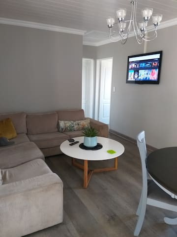 Lounge with a TV and sleeper couch. DSTV and Netflix are available.