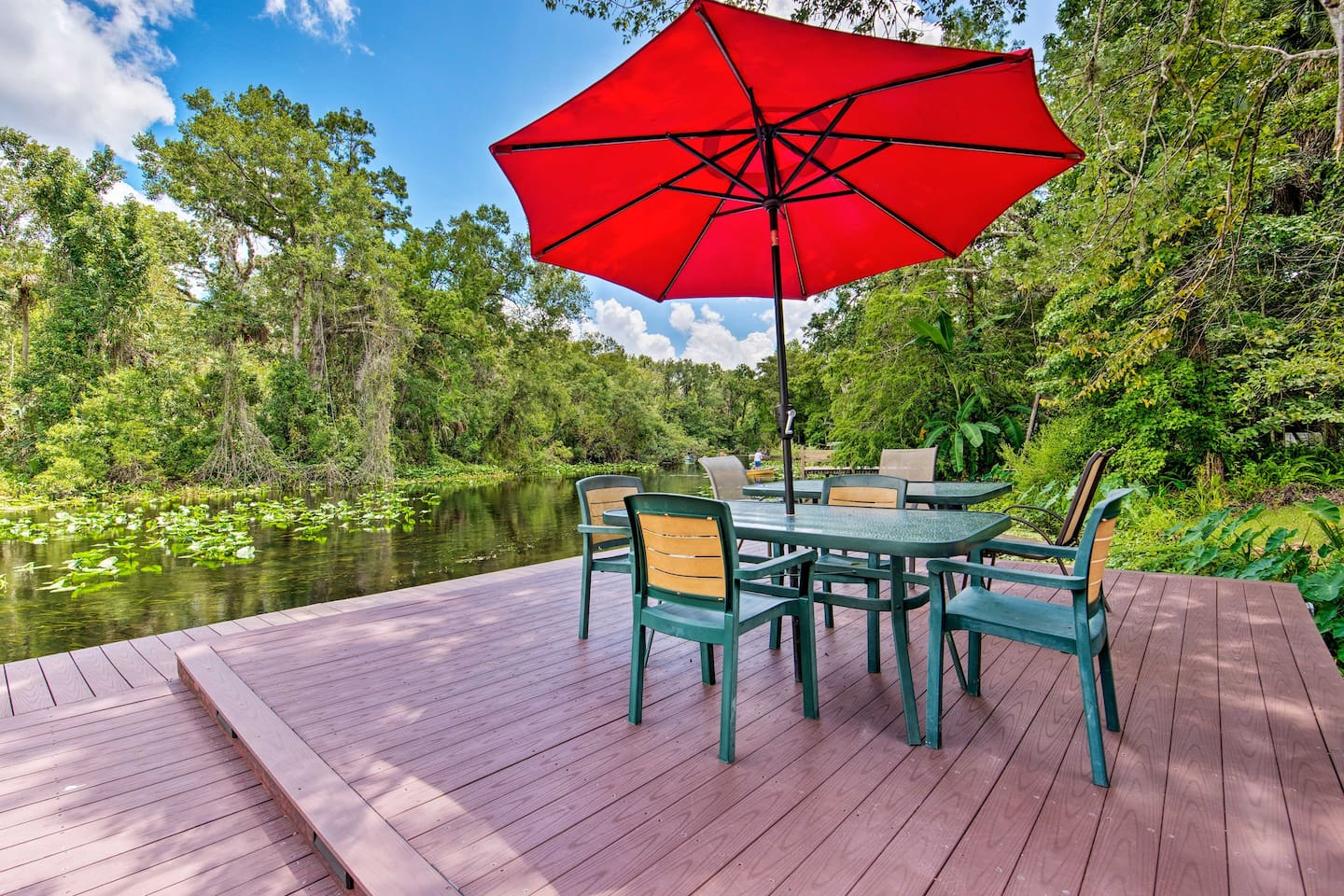 Relax with a drink on the riverfront deck of this Apopka vacation rental!