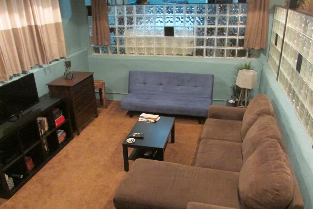 spacious sunken living room with sleeper sofa bed and fouton