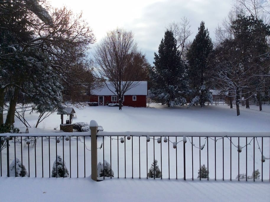 View of the barn in the winter with a beautiful yard and setting.