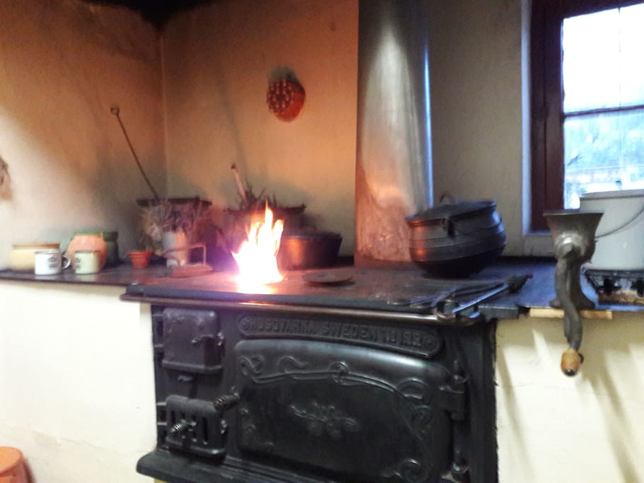 Wooden stove in the kitchen with fire burning in cold winter nights