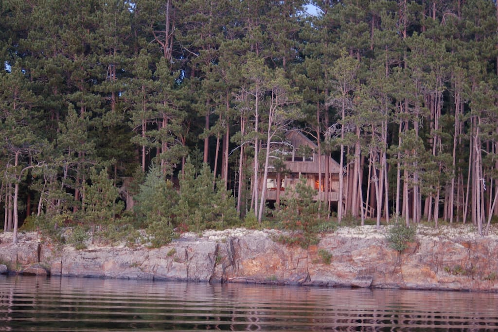 Cabin sits on a rocky bluff overlooking the lake.