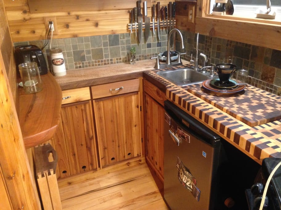 Kitchen includes refrigerator, coffee and tea fixings, plates, bowls, pans, utensils  and such to cook a meal.