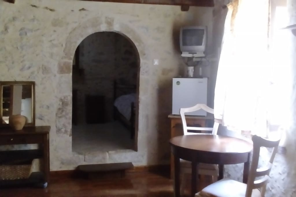 Petit salon avec frigidaire et télévision, bouilloire.