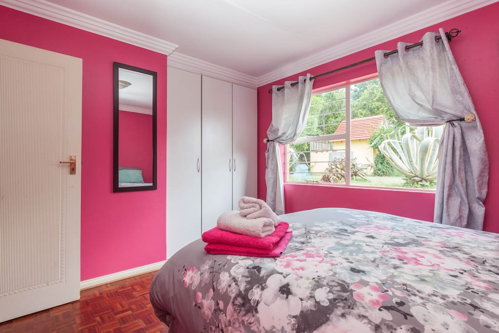 Bedroom with built-in cupboards and view onto garden