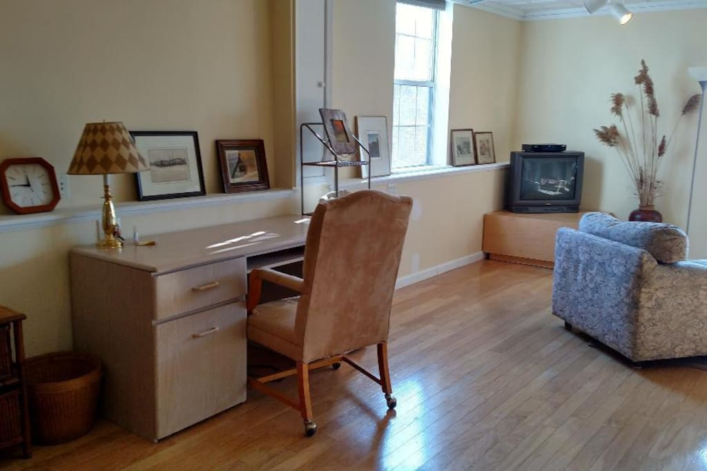 executive desk and chair with wheels; desk pulls out to an L-shape desk on the right; office supplies in drawers, lamp