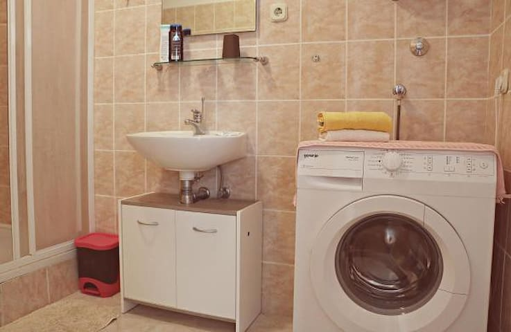 Bathroom in which you can also find a washing machine.