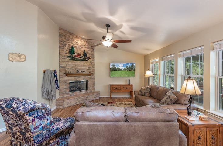 The open and bright living room features a smart TV, fireplace, and spacious windows that bring the outdoors indoors.
