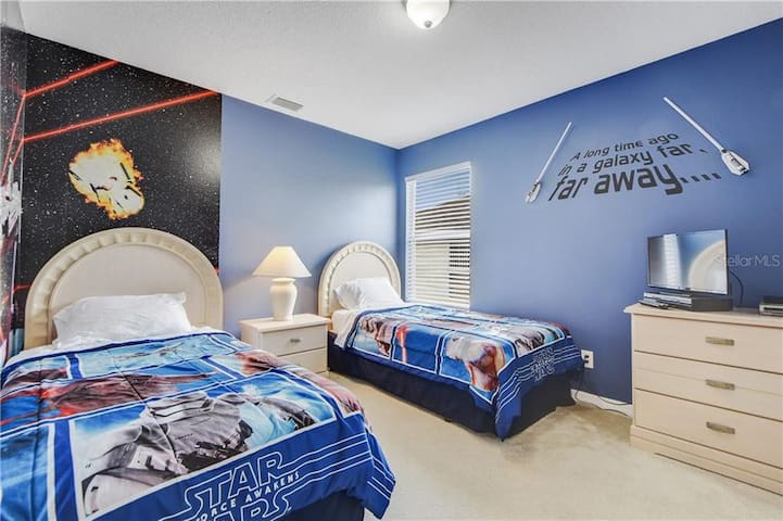 This Star Wars themed room features twin beds and a flat screen TV  The twin bedrooms share a bathroom which offers a shower, bath tub, sink and toilet