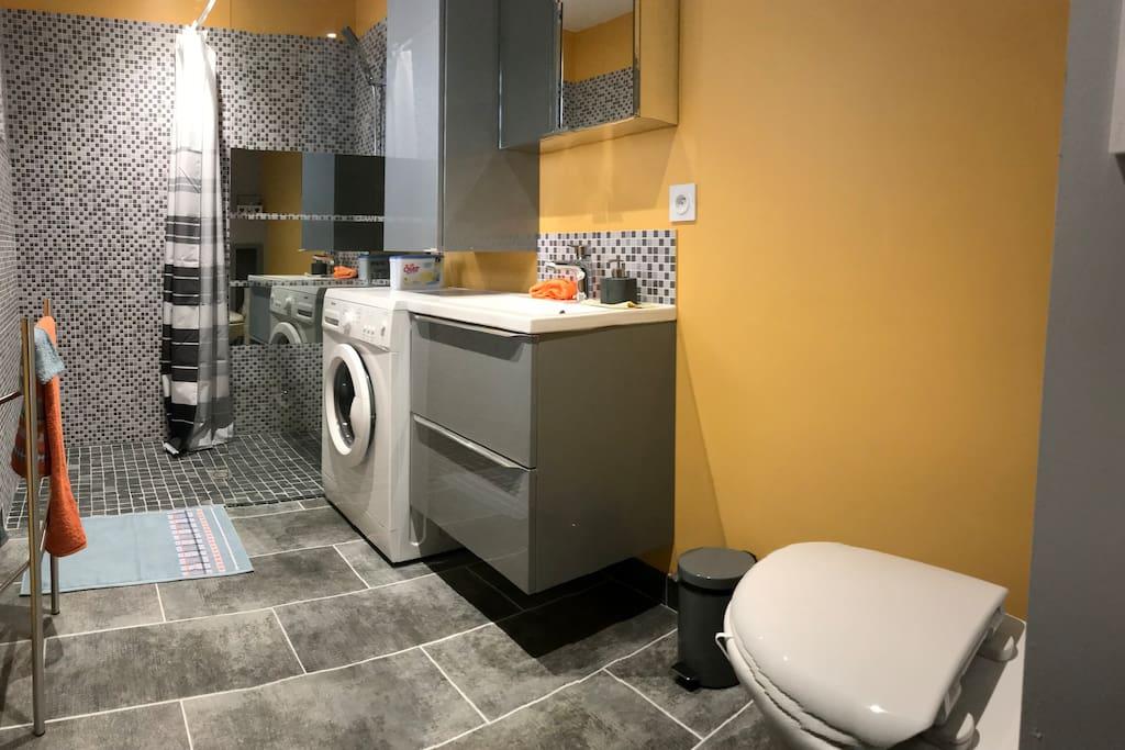 Une salle de bain douche/WC équipée de nombreux rangements et d'un lave-linge