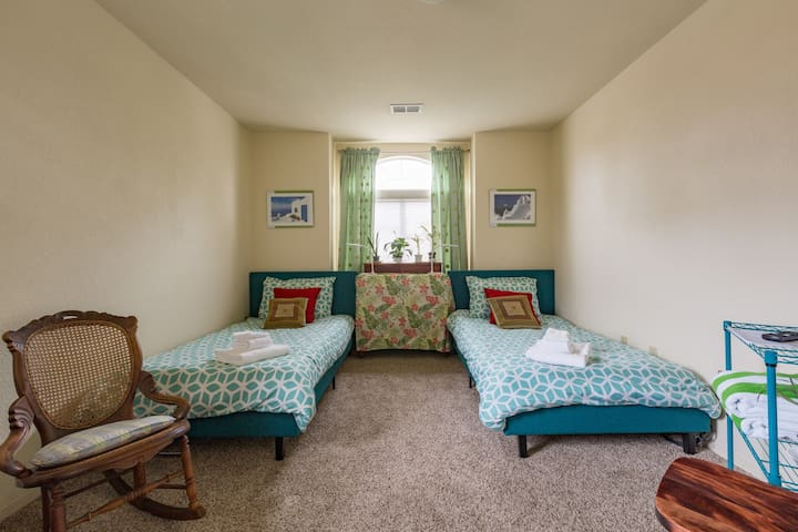 The twin bed room includes TV, desk, rocking chair, walk-in closet and coffee station.