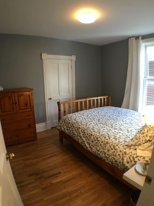 Hardwood floors, dresser and window with black-out curtains.